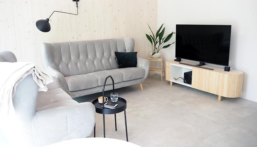 Minimalistyczno-eklektyczny salon w drewnianym domu w lesie